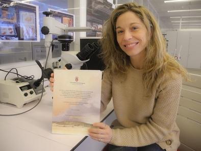 Martínez de Pinillos posa con el certificado del premio a su tesis.